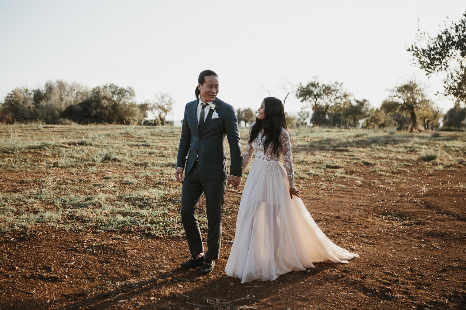 Bride and groom walking through field in Italy for their italian destination wedding