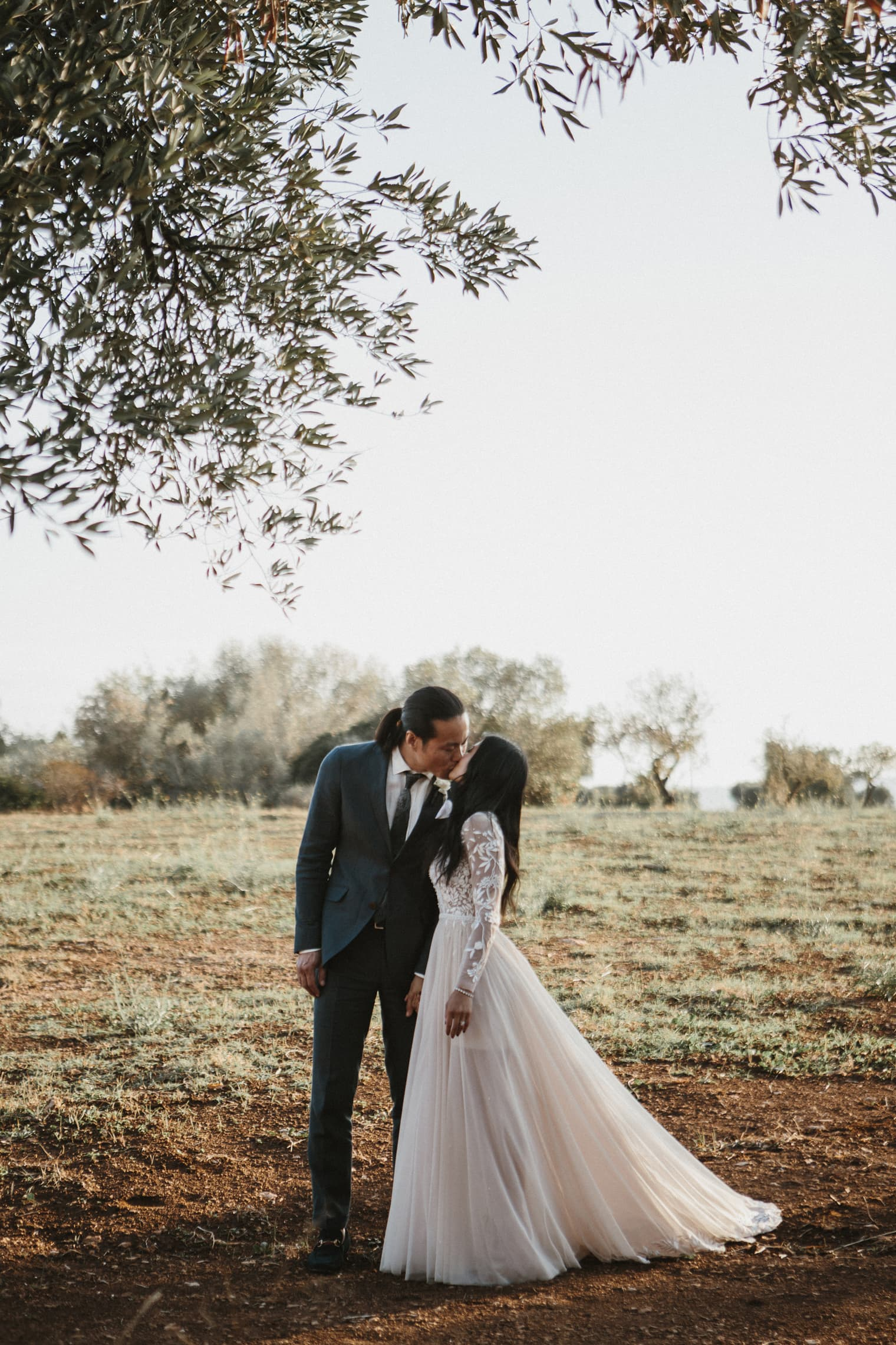 italy wedding photographer captures bridge and groom kissing under olive trees in Puglia