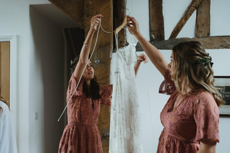 Bridesmaids holding up Rue De Seine wedding dress