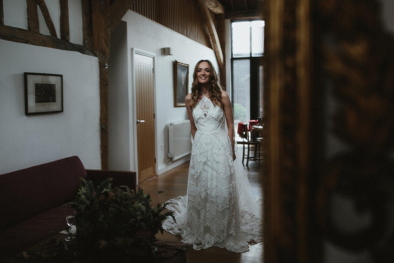 Bride looking at herself in rue de seine wedding dress in mirror ahead of her outdoor wedding in essex