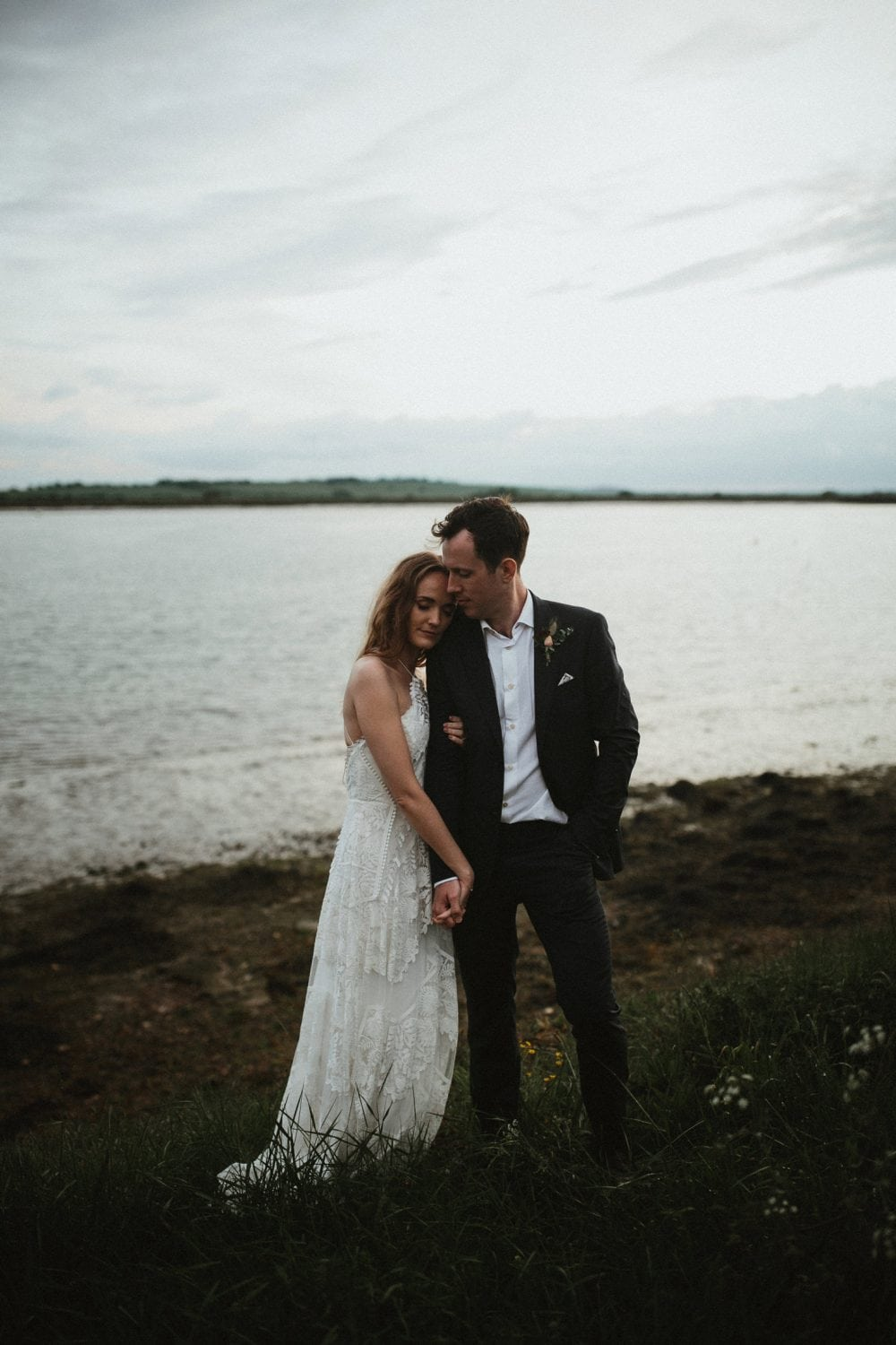 Couple together by estuary for their outdoor wedding in essex