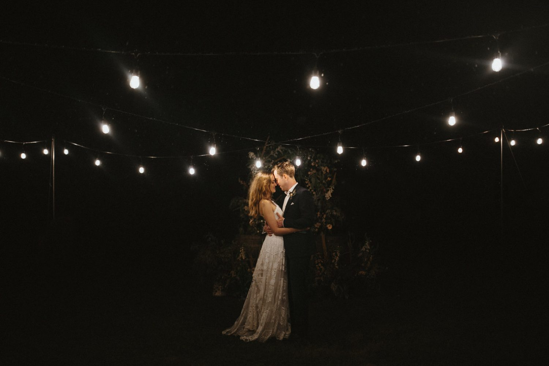 Bride and groom under festoon lighting during their outdoor wedding in essex