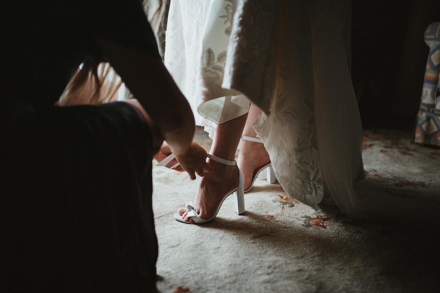 Bridesmaid helping tie bride's shoes