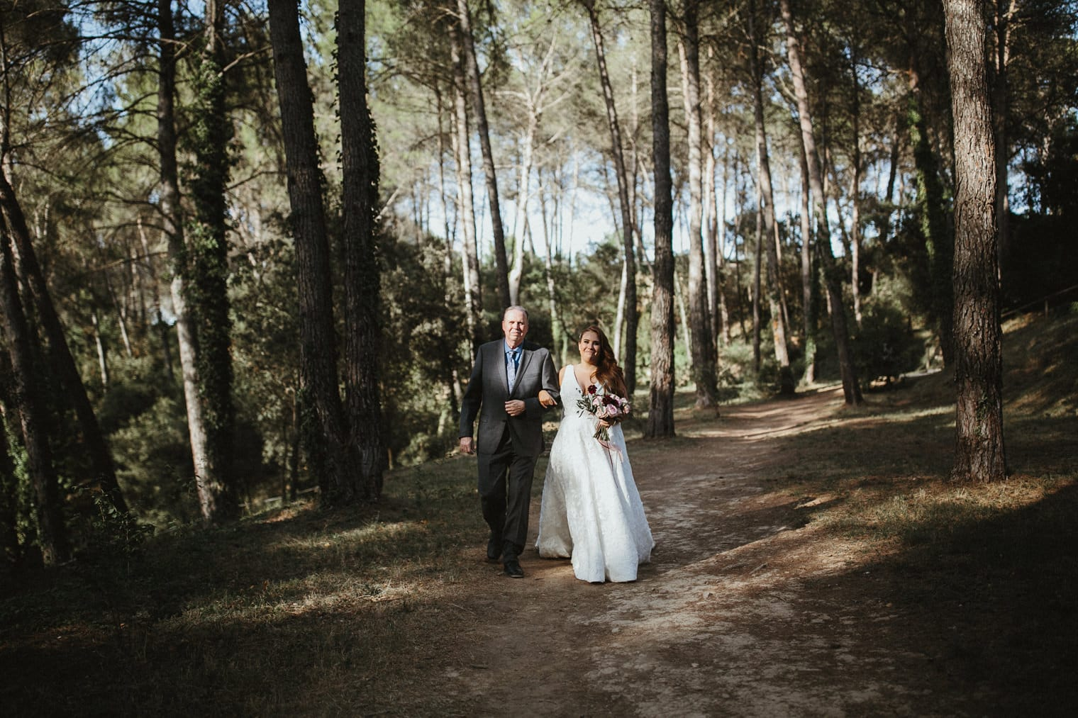 Father walking bride down the aisle in forest wedding