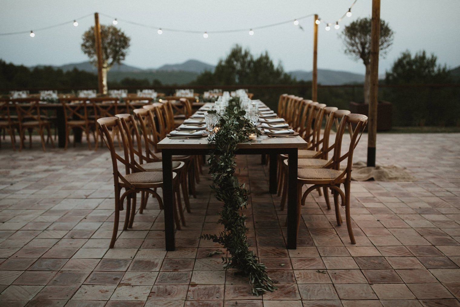 Outdoor wedding reception decor under festoon lighting in spain