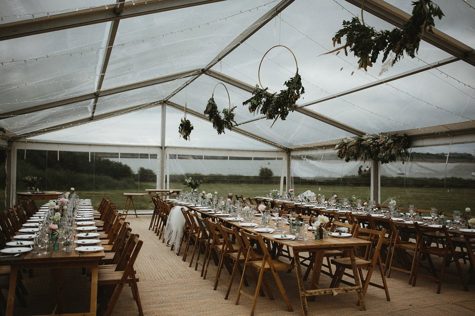 transparent marquee for outdoor wedding in essex with green foliage