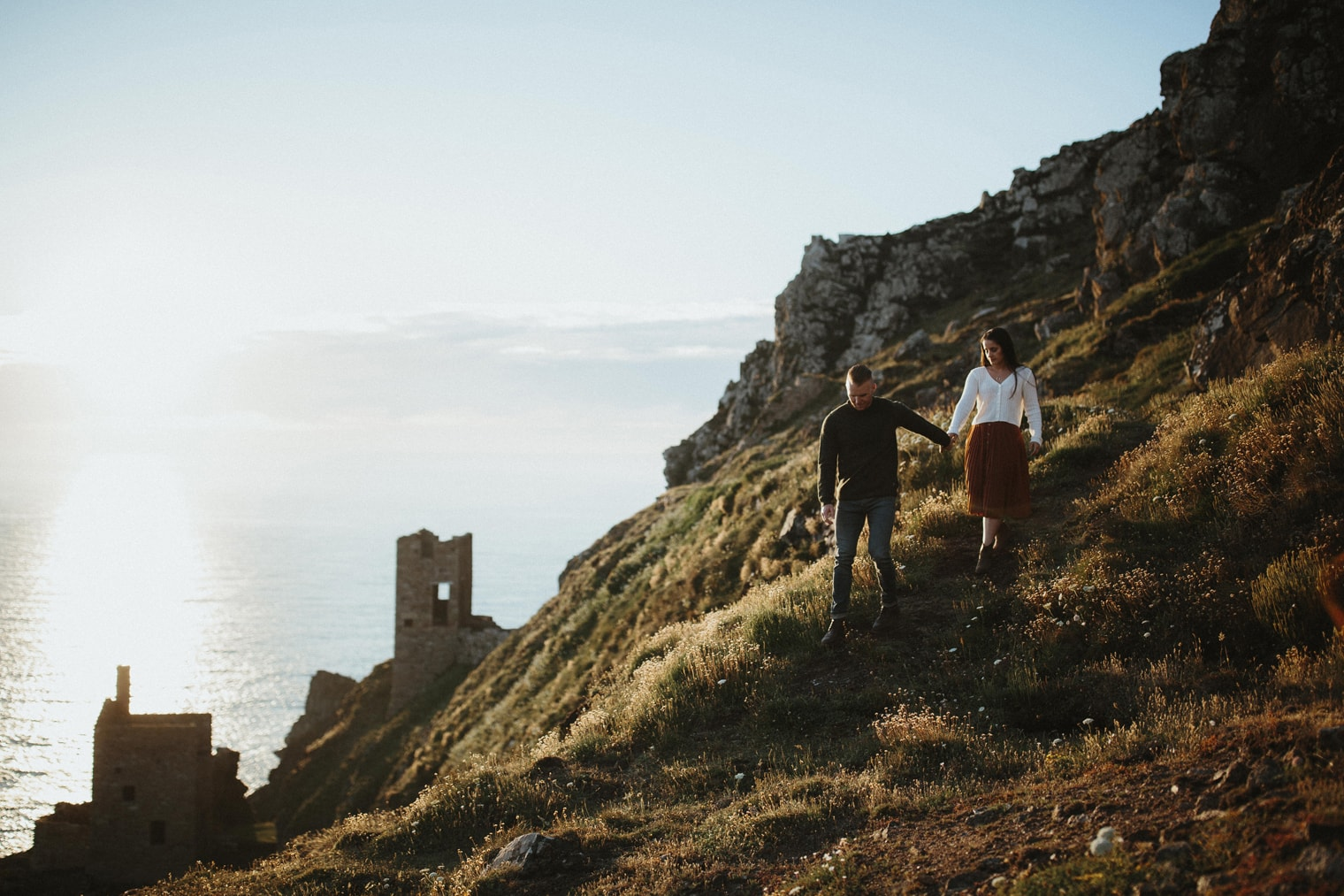 man leading woman down hill in Cornwall during engagement session