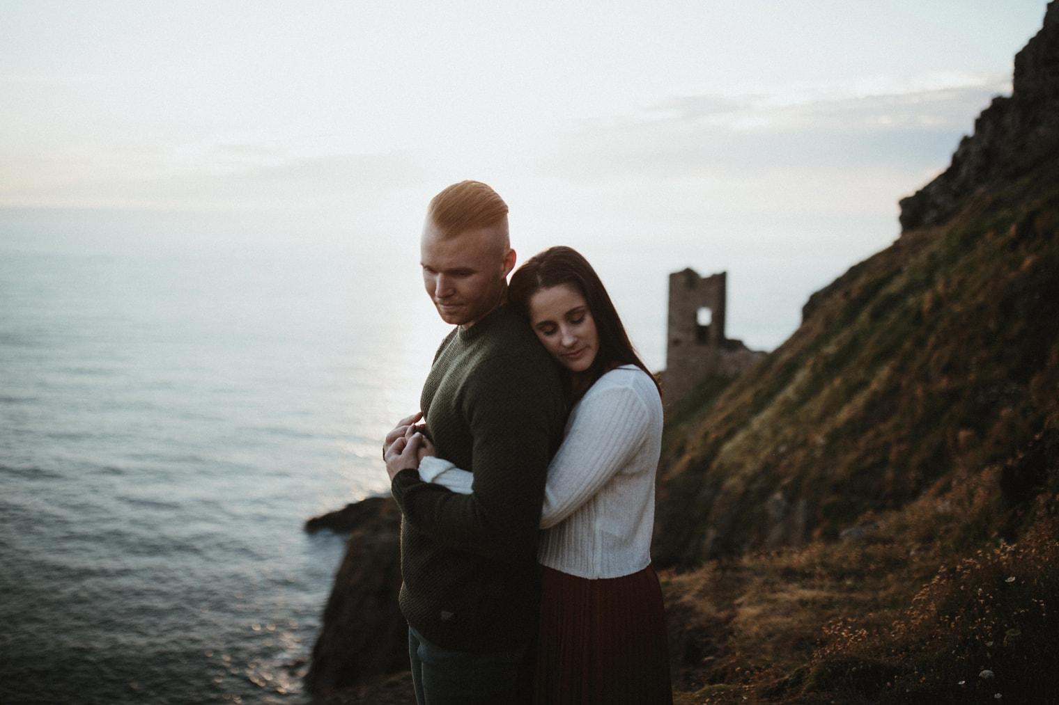 woman hugging man during engagement shoot in cornwall