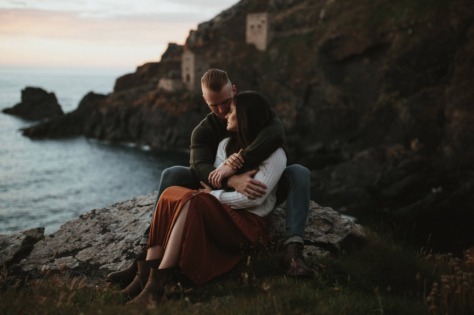couple cuddling on the cornish coastline with a tin mine in the background