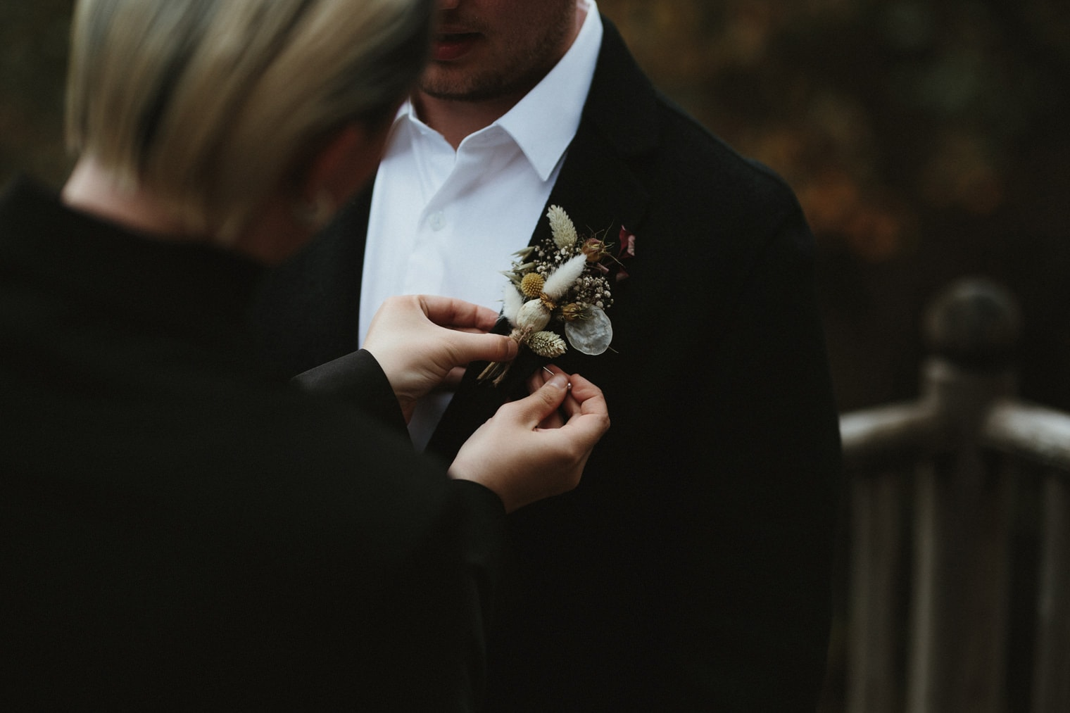 dried flower boutonniere being placed on groom ahead of autumn elopement in the scottish highlands