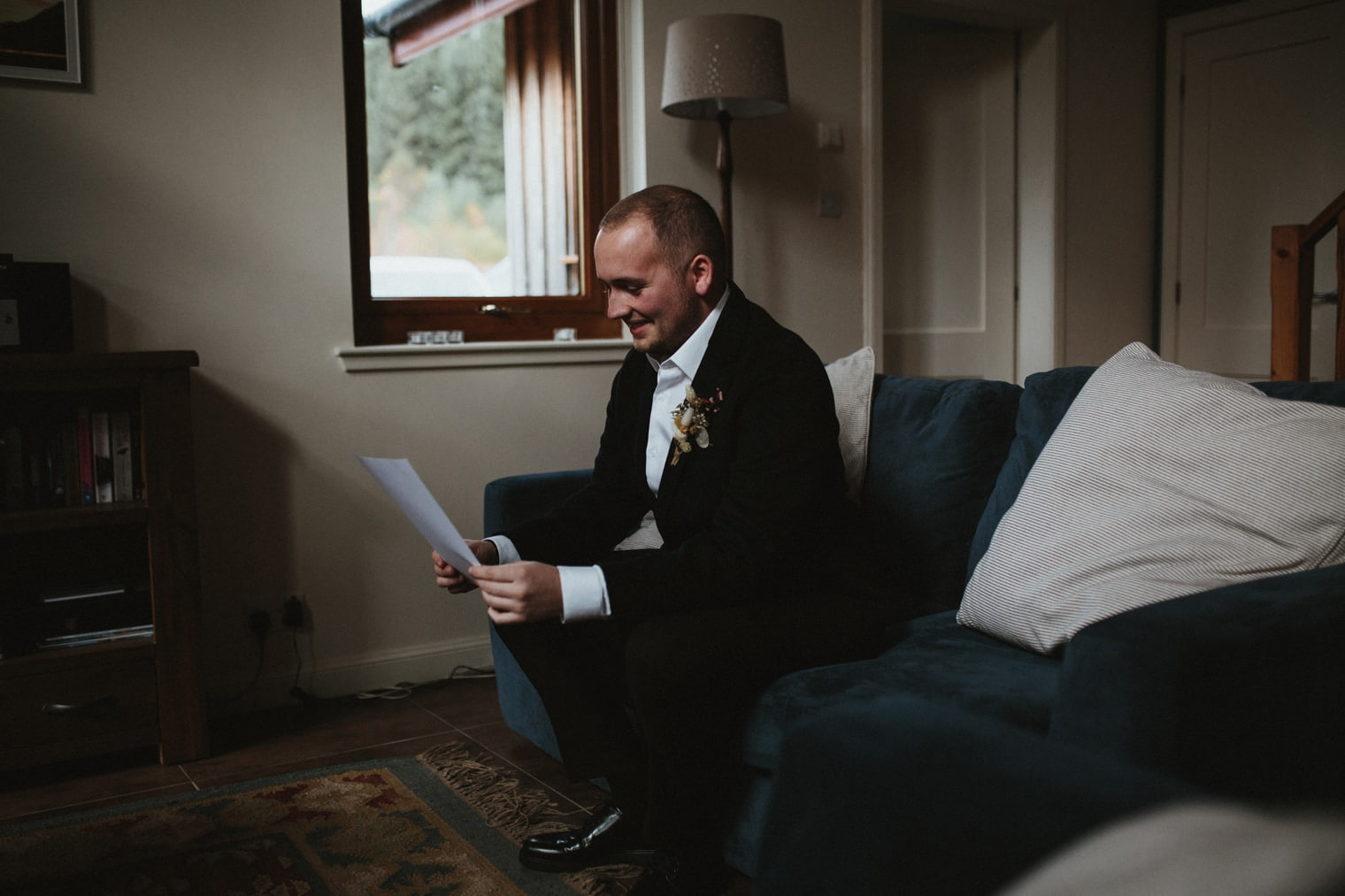 groom reading letter from bride ahead of their elopement