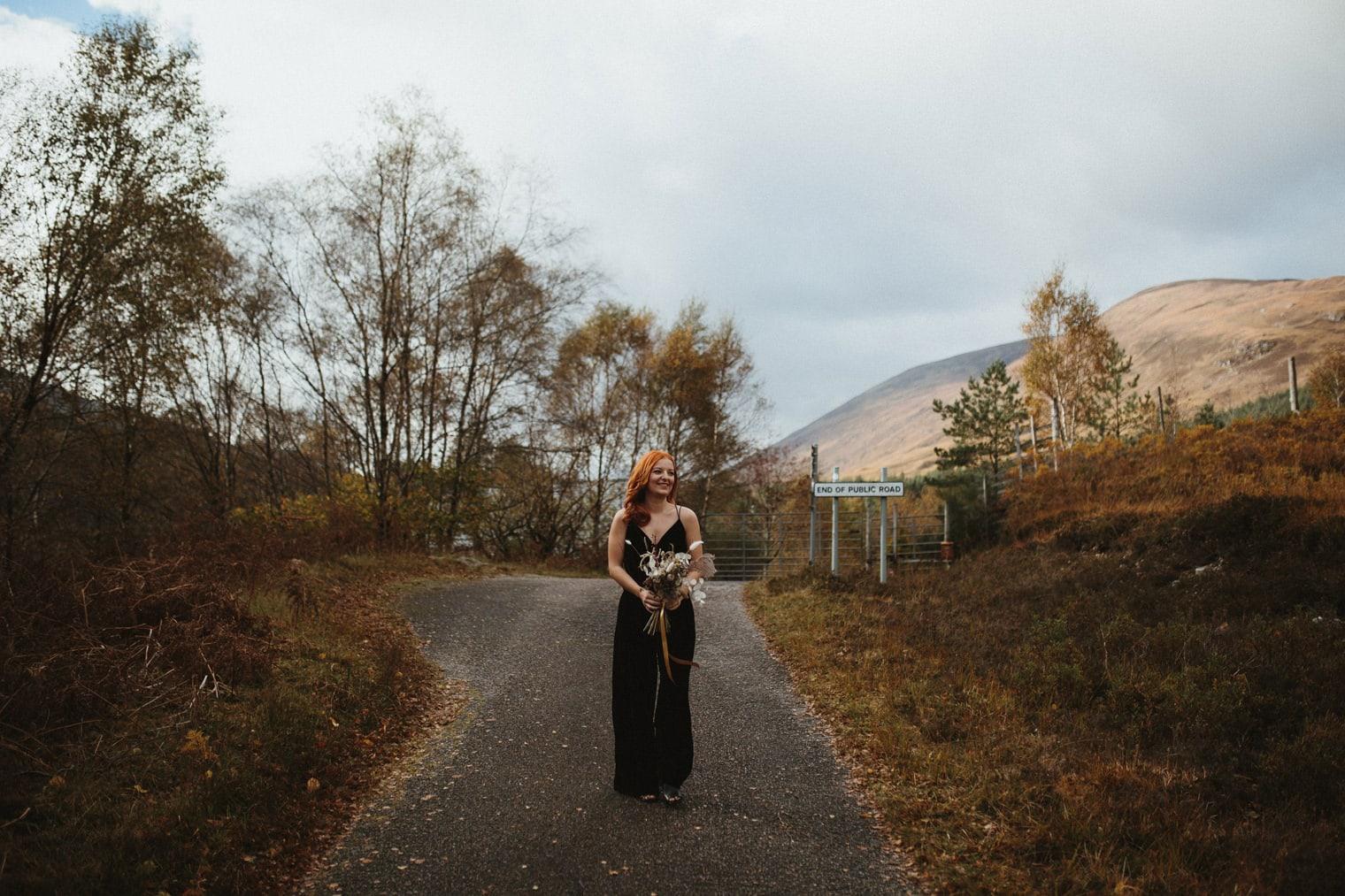 bride wearing black velvet jumpsuit walking to greet groom for first look