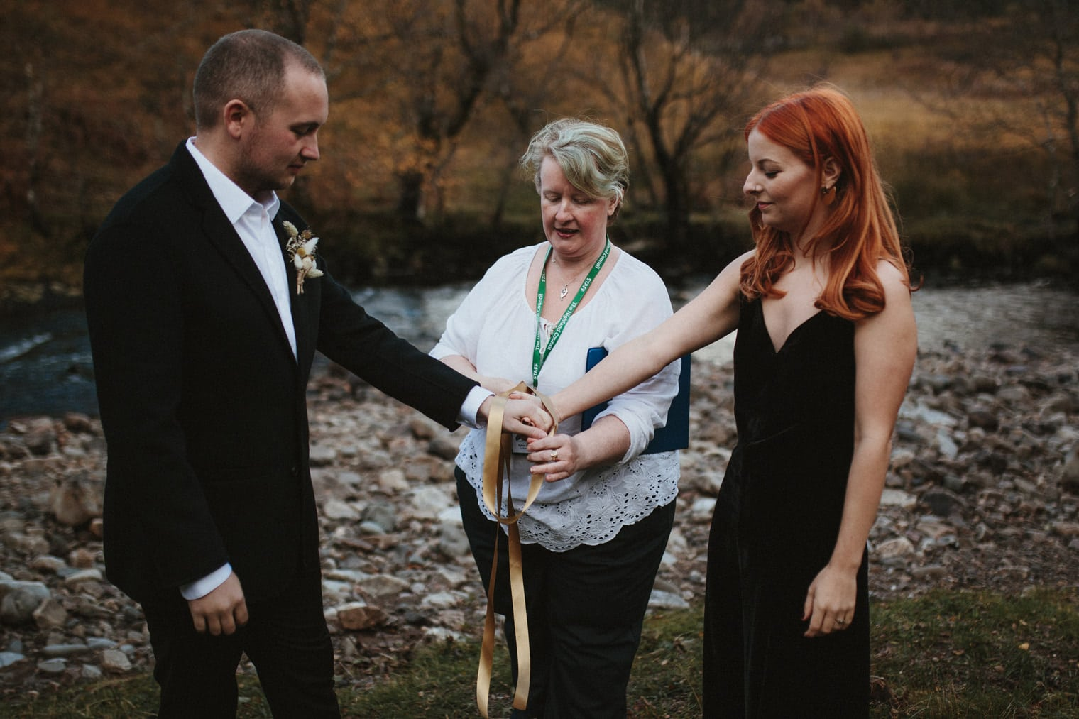 couple having a handfasting ceremony in the scottish highlands