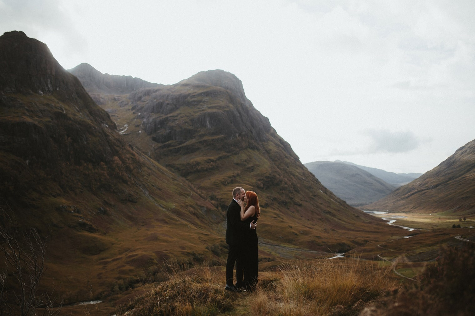 Couple kissing on top of mountain in Glencoe during their autumn elopement in Scotland