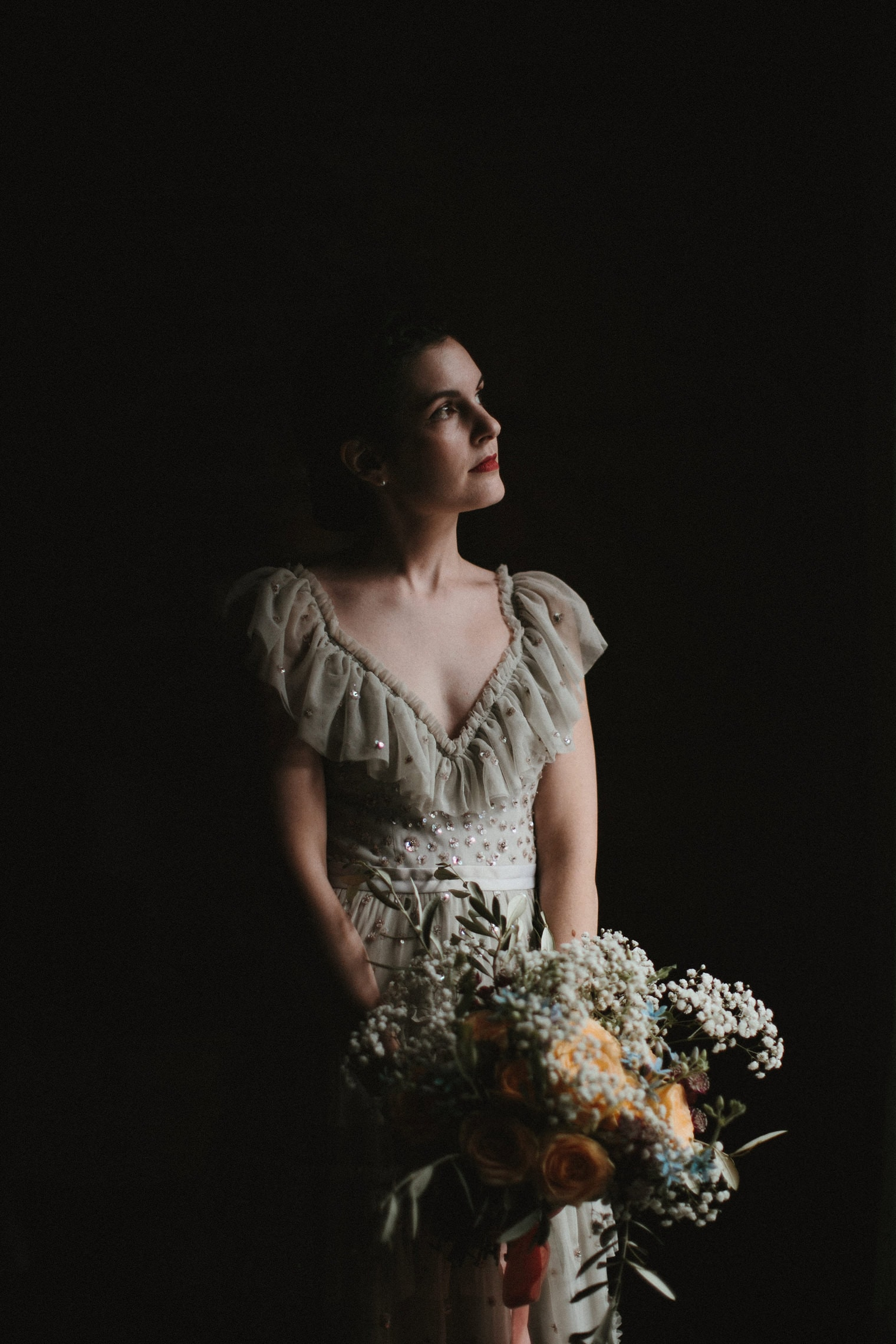 Beautiful bride with floral bouquet looking out the window wearing grey and sparkly needle and thread wedding dress