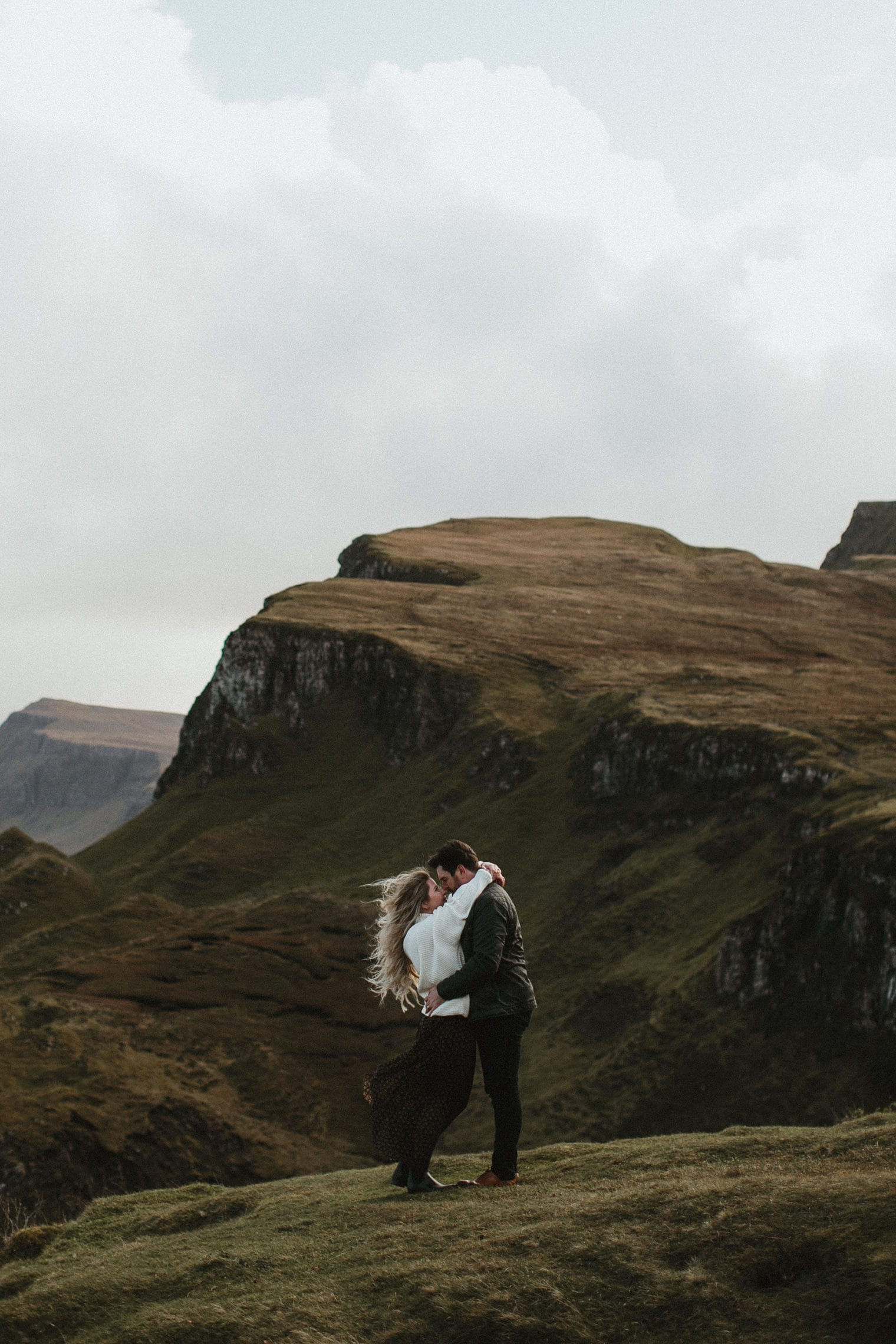Couple hugging each other in the wind during adventurous anniversary shoot in Isle of Skye