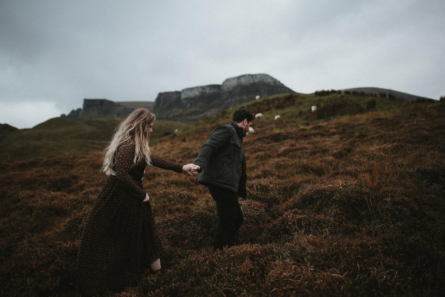 couple climbing hill in scotland