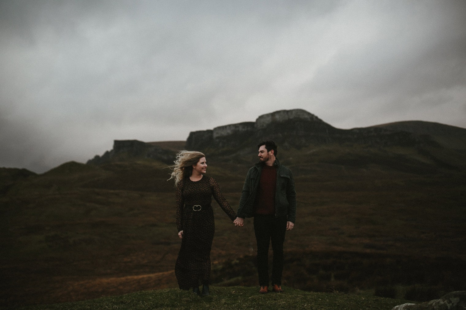 Couple holding hands together in Isle of Skye with Mountains in the background
