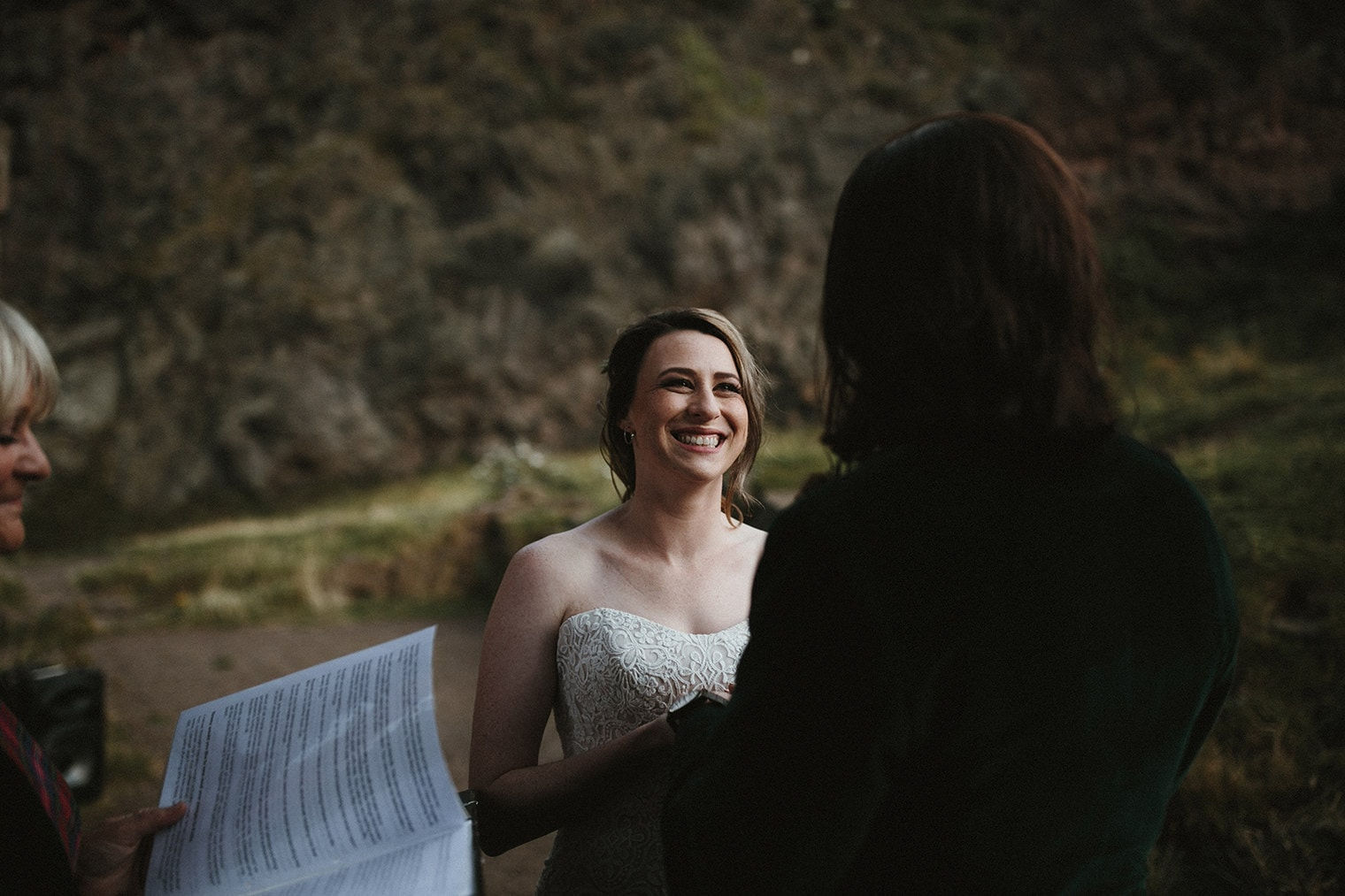 Bride smiling at groom during her wedding ceremony at St. Anthony's chapel in edinburgh