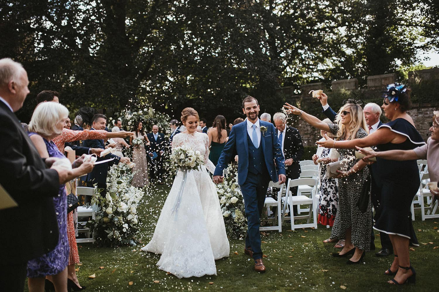 Bride and Groom having confetti thrown at them after wedding ceremony at Durham Castle