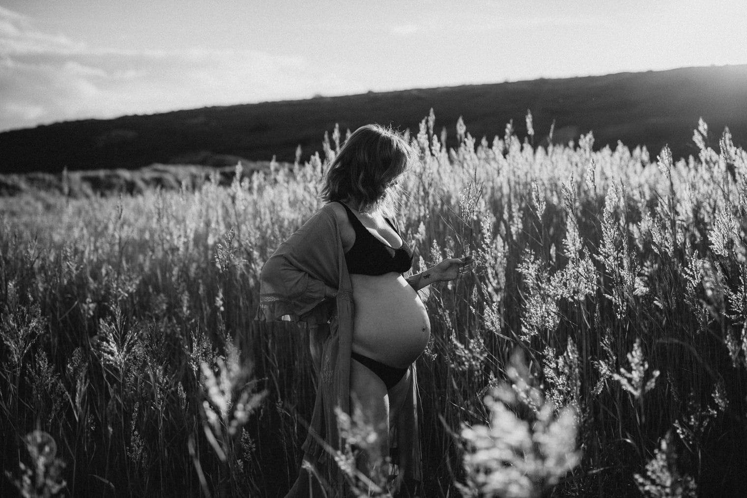 Mother to be amongst a field of reeds in Cornwall