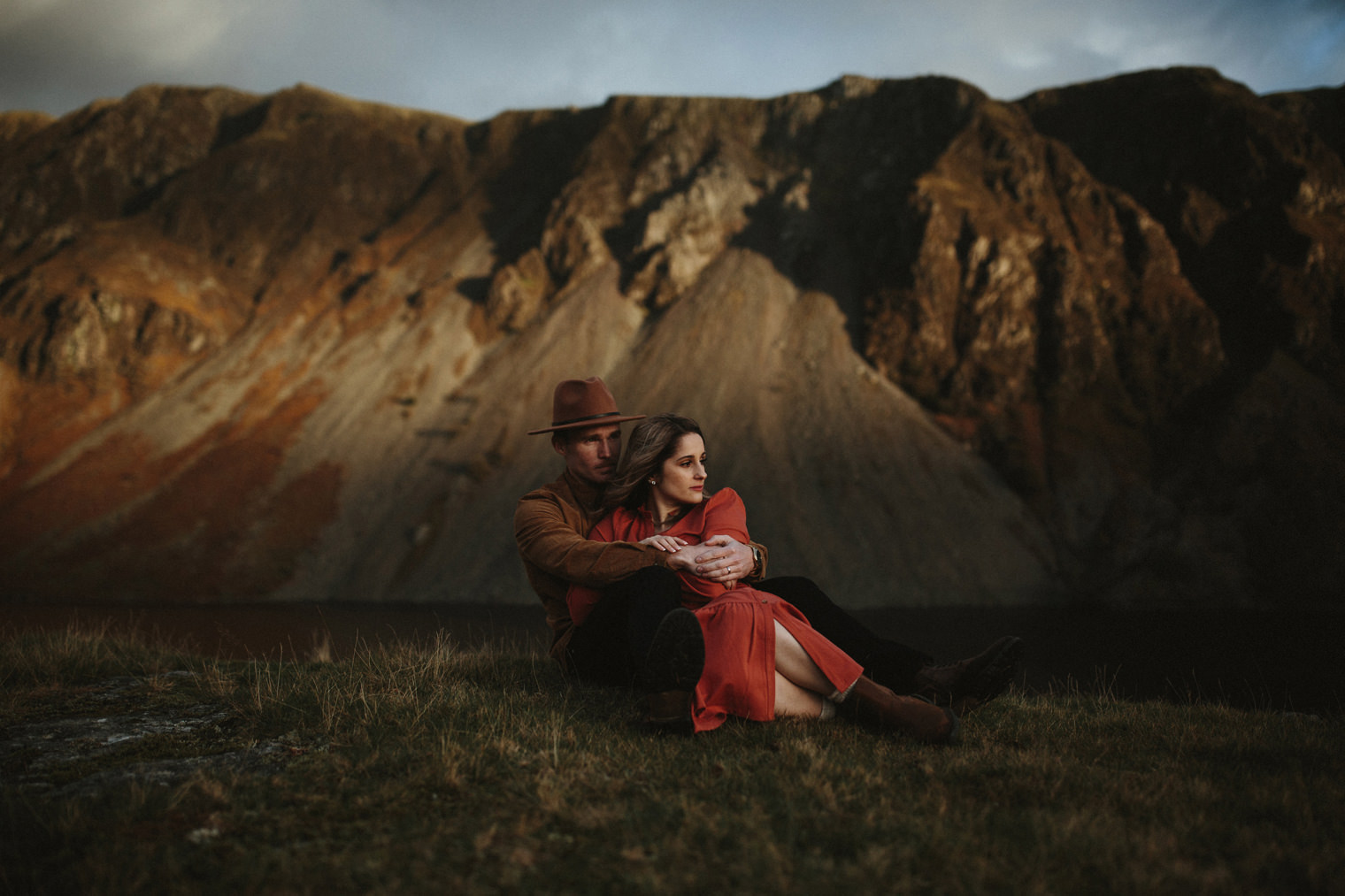couple laying on the ground together cuddling in the lake district with stunning light hitting the mountains behind them