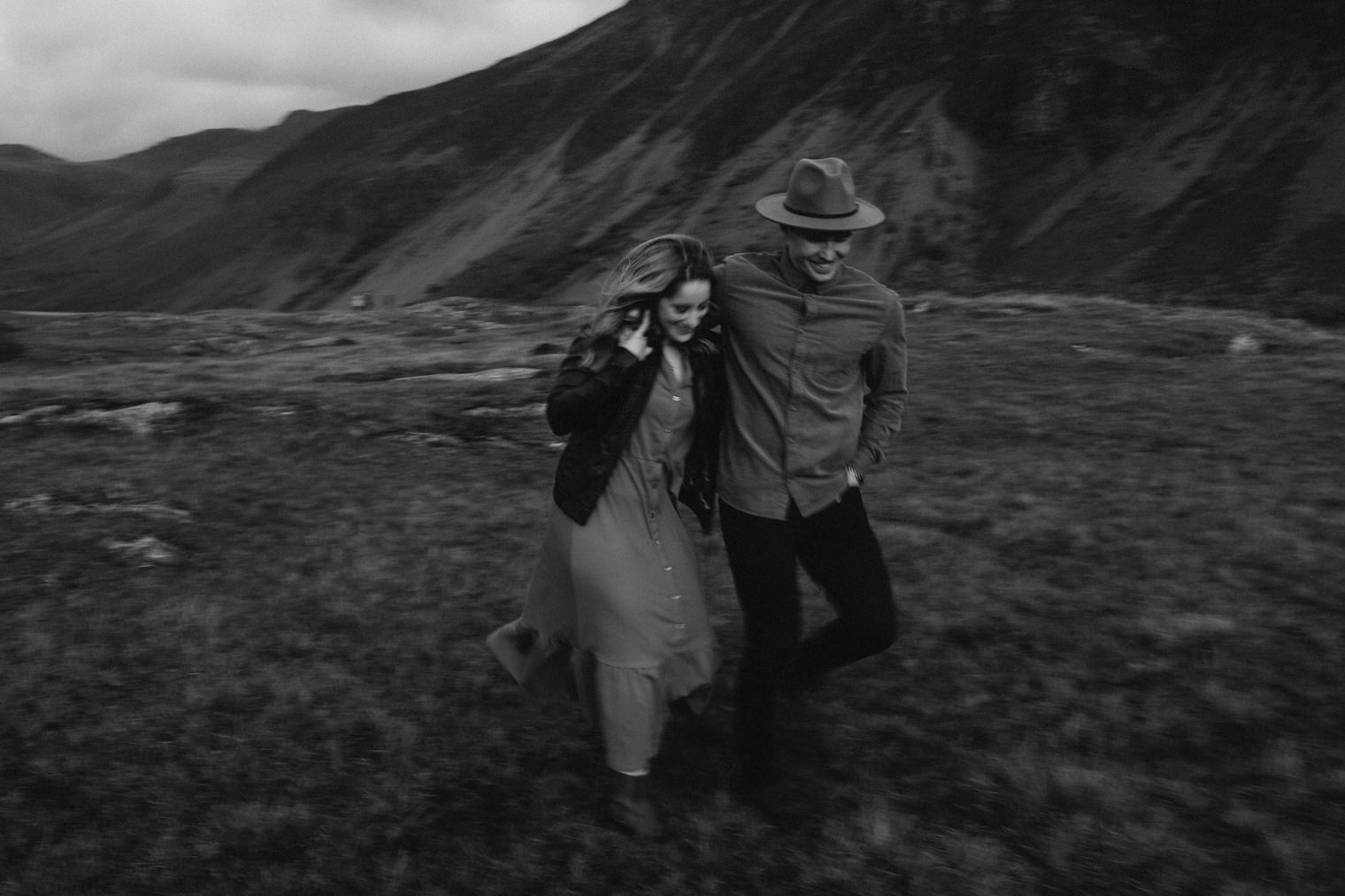 couple running together in the lake district during their couples portrait session in the lake district
