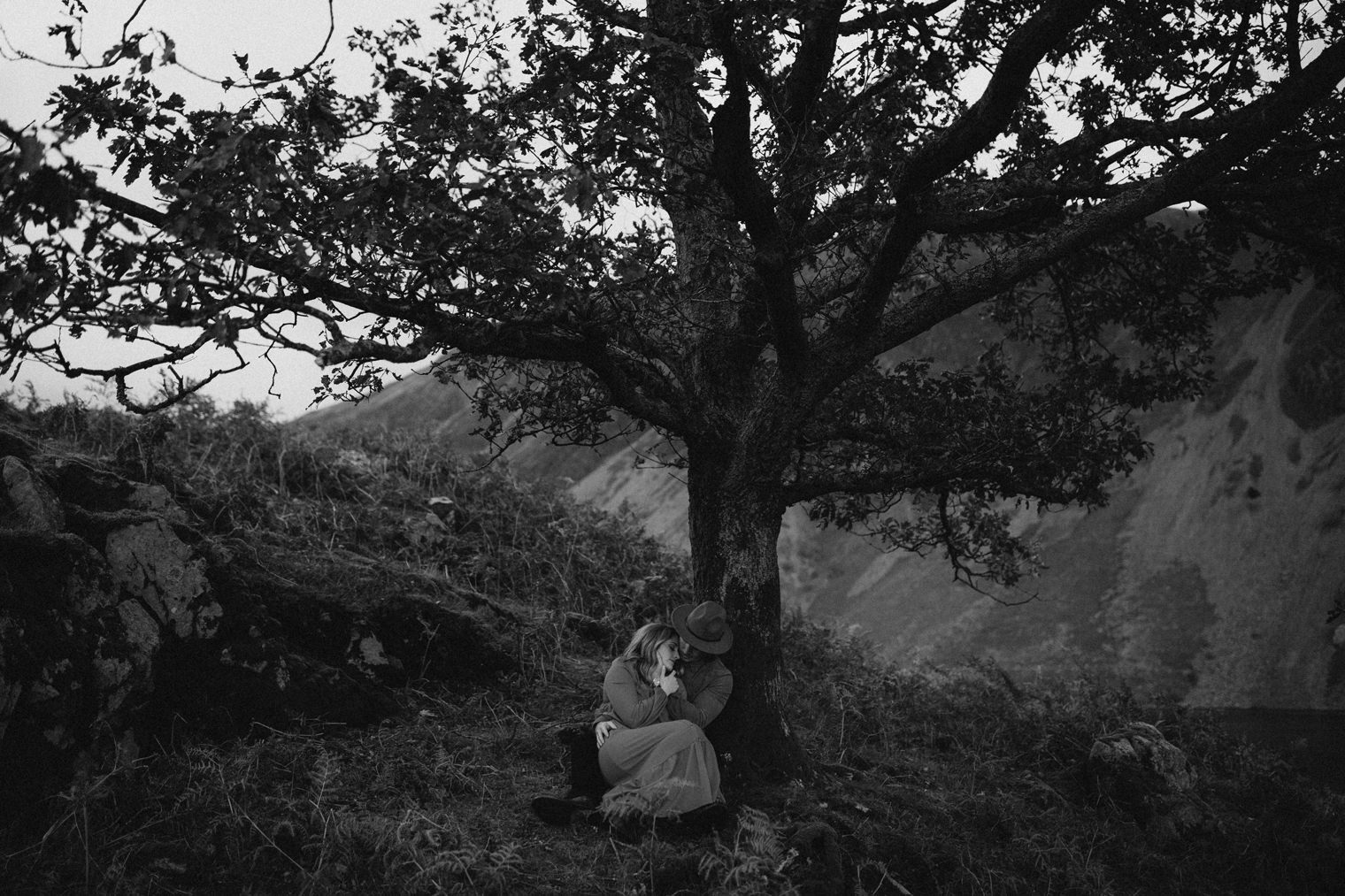 couple cuddling beneath a giant tree in the Lake District