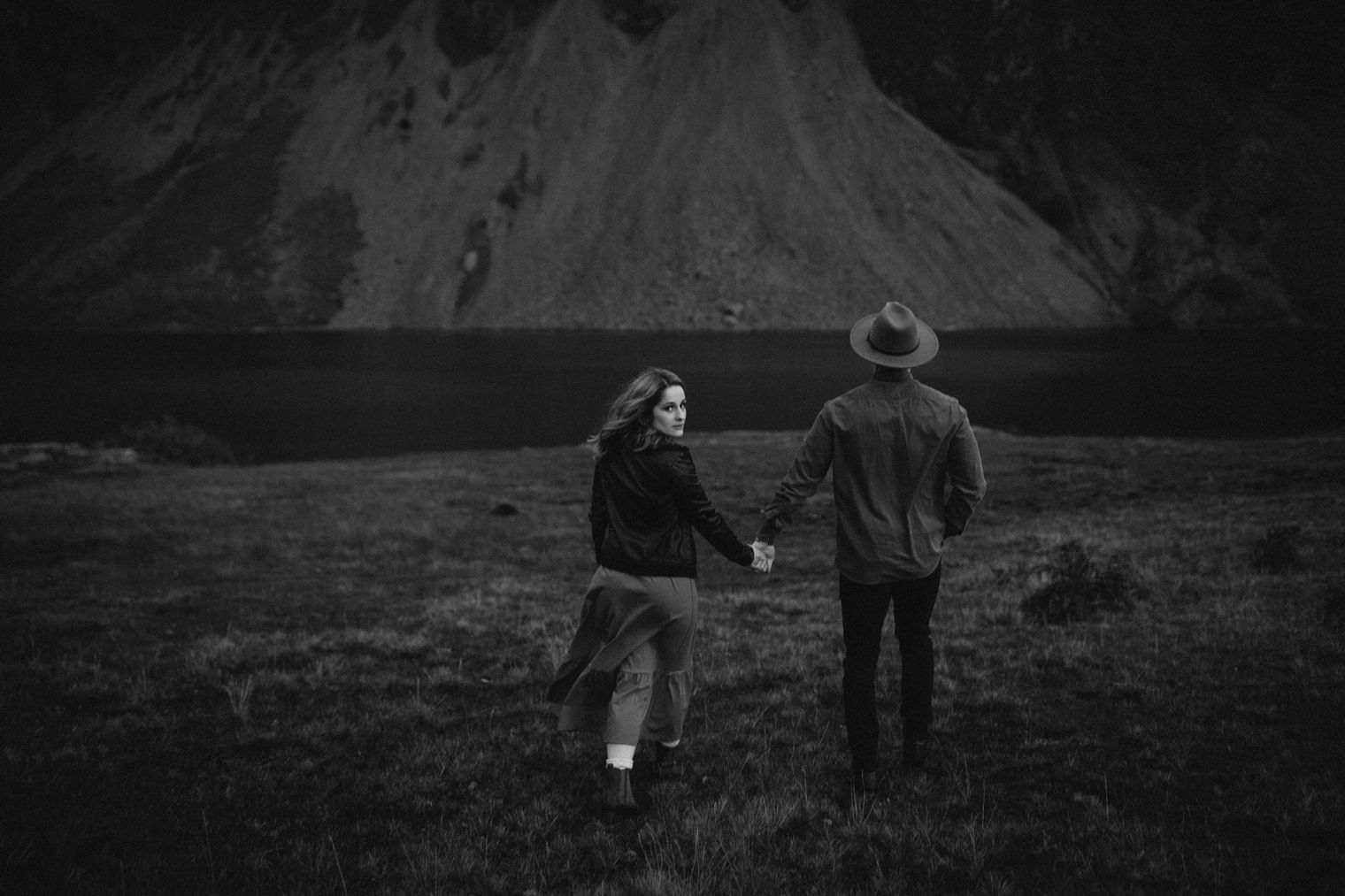 black and white photograph of couple with the woman looking back to the camera during their Couples Portrait Session in the Lake District